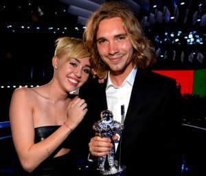 Miley Cyrus poses with homeless youth Jesse Helt at the 2014 VMAs Photo Credit: US Magazine