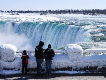 Visitors take in the rare site of the frozen Niagara Falls on February 20th.  Photo Credit: CBS News