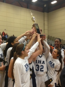 Katie Jones '17, Caitlin Roche '15, Rebecca Garcia 16, Jordan Wilmoth 16, Katia Oge '15, along with other teammates lift their trophy up together.