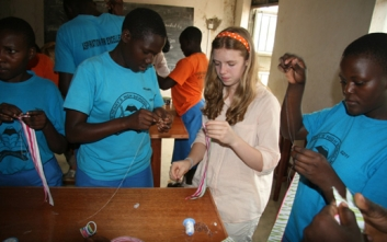 Mary Grace Henry teaches young girls in Africa how to make hair accessories.  Photo Credit: One World Youth Project