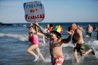 Man holds a sign as he runs into the freezing cold Atlantic Ocean on February 21 in Seaside Heights, NJ. This year's Plunge raised over $2 million for the Special Olympics. Photo Credit: Yahoo News