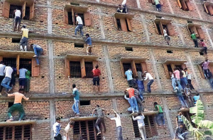 Parents and other family members are caught climbing a four-story building to give cheat sheets to the students taking the board exams inside. Photo Credit: ABC News