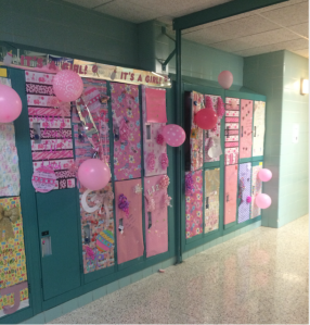 "Freshmen lockers decorated pretty in pink with ""It's a Girl!"" signs and rattles taped to the lockers by the juniors to show love to their baby sisters. Photo courtesy of Emily Ash'19"