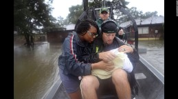 A mother and her three-week old baby are rescued by a volunteer. Photo courtesy of CNN