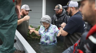 Volunteers rescue an elderly woman from her home. Photo courtesy of CNN
